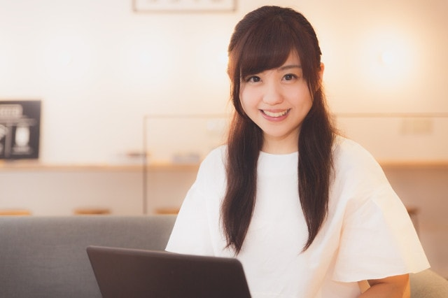 ノートパソコンと白Tシャツの女性